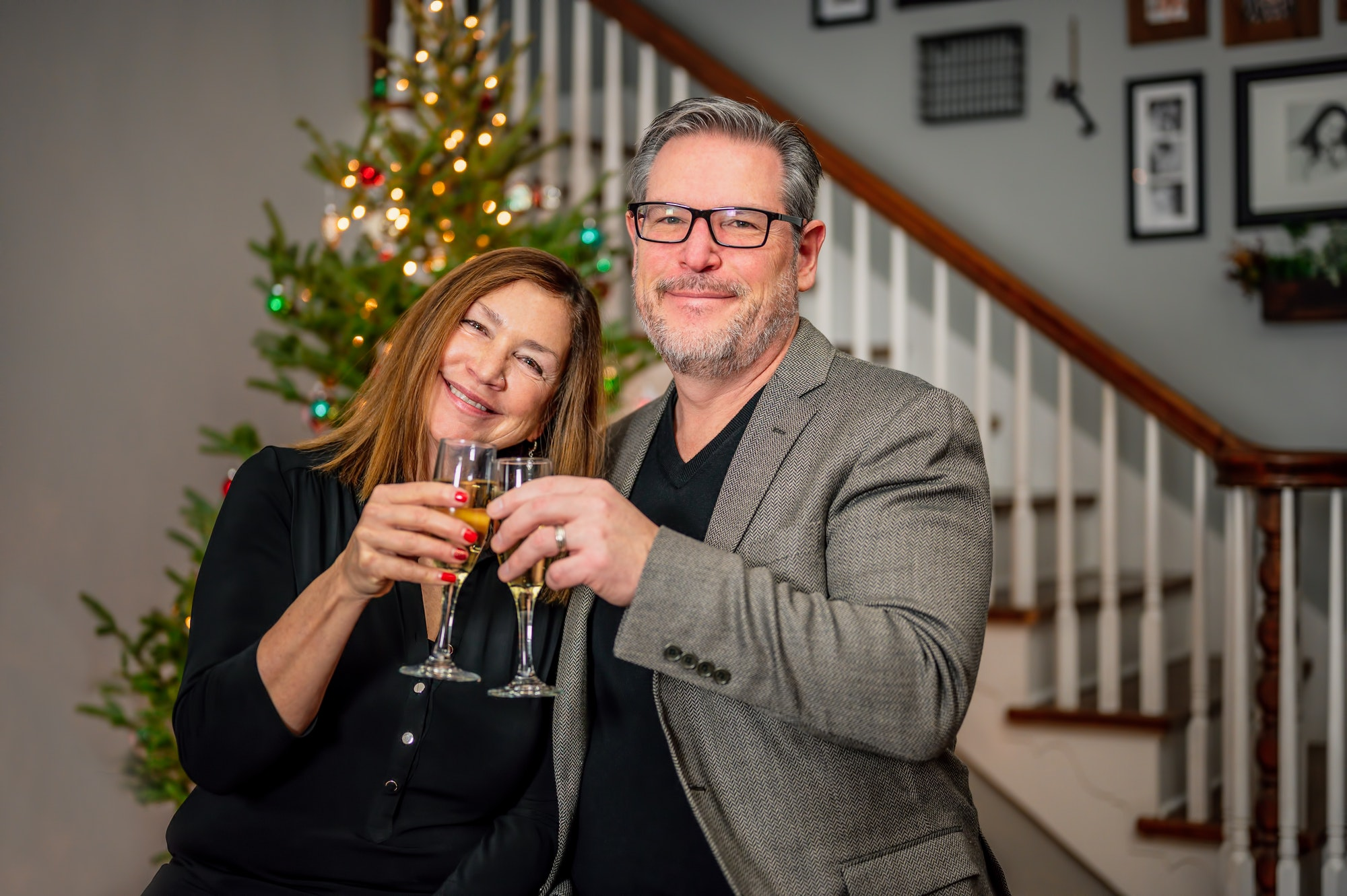 Smiling couple celebrating wedding anniversary at home with glass of champagne